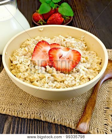 Oatmeal with strawberry on dark board