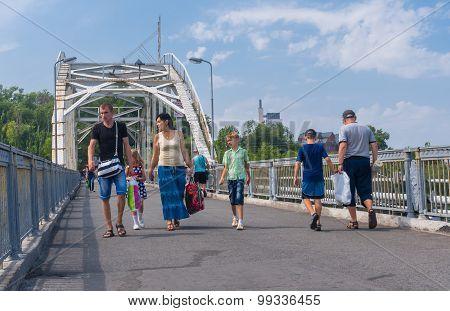 Group of people walking through pedestrian bridge