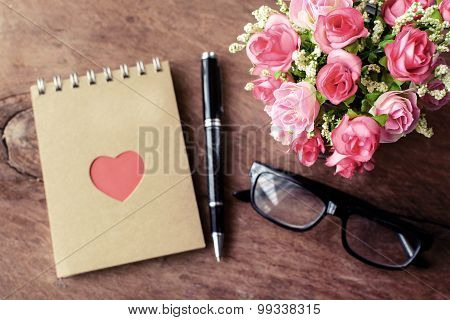 Flower With Blank Notepad And Pen On Old Wooden Background