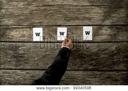 High Angle View Of Web Developer Placing Thre White Papers Spelling Www On A Textured Rustic Wooden
