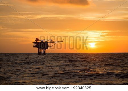 Offshore oil and rig platform in sunset or sunrise time. Construction of production process
