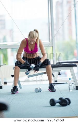 halethy young woman exercise with dumbells and relaxing on banch in fitness gym