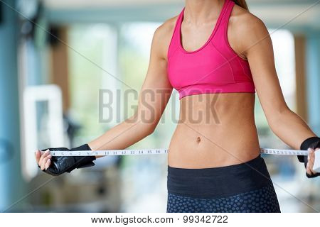 young fit woman measuring belly on a training  in  fitness gym