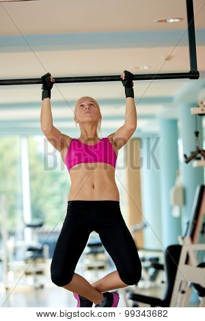 healthy lifestile, young woman in fitness gym lifting on bar and working on her back and hands muscles