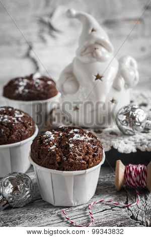 Chocolate Muffins And Ceramic Santa Claus On A Light Wooden Surface, Vintage Style