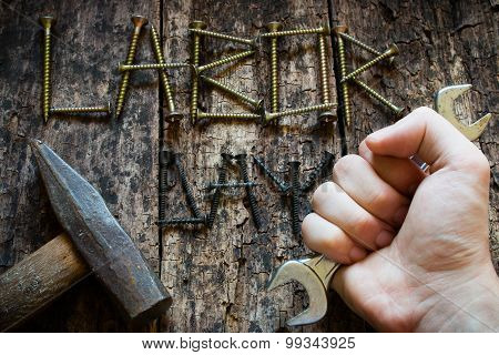 Man Holding A Wrench In His Hand On The Background The Inscription Labor Day Selective Focus