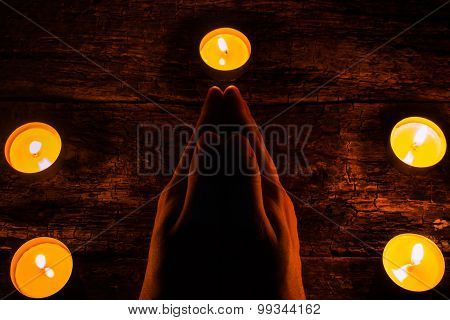 Man Reads A Prayer Surrounded By Candles