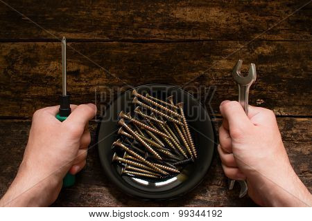 Worker With Wrench And Screwdriver In His Hand Next To The Plate With Screws