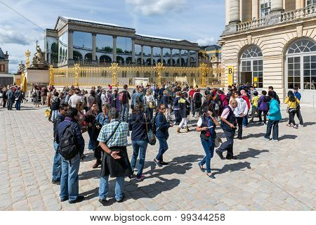 Visitors Waiting In A Queue To Visit The Palace Of Versailles, Paris, France