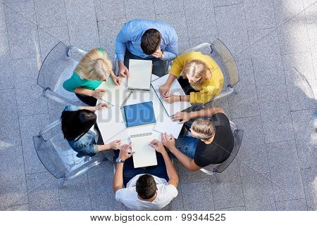 top view,  group of students together  at school table working homework and have fun