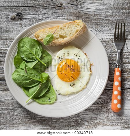 Fried Egg And Fresh Spinach On A White Plate On A Light Wooden Background, Healthy Breakfast, Snack