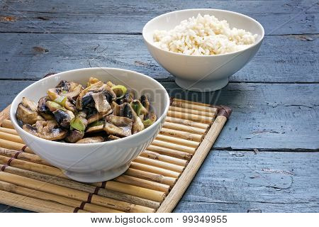 Mushroom Vegetables And Rice In Bowls On A Bamboo Mat And Rustic Blue Wood