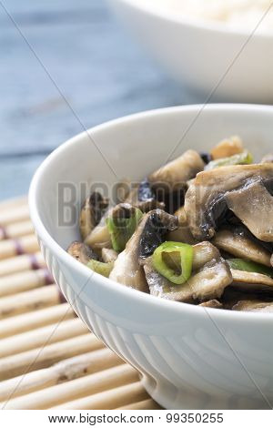 Mushroom Vegetable Dish In A White Porcelain Bowl On A Bamboo Mat, Closeup, Vertical