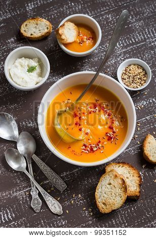 Pumpkin Soup With Paprika, Flax Seeds And Cream In A White Bowl On A Dark Wooden Background