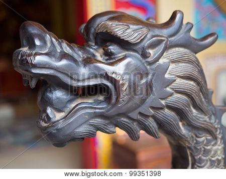 The carved wooden head of a black dragon.