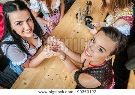 Two attractive women at Oktoberfest with traditional Dirndl dresses, holding her hands, best frinds