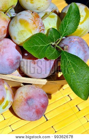 Fresh Plums In A Wicker Basket With Green Leaves