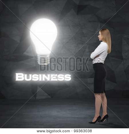 Side View Of Young Business Lady Who Is Looking At The Huge Lightbulb And The Word ' Business '. Con