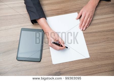 Closeup Of A Business Woman's Hands While Writing Down Some Essential Information. There Are Tablet