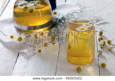 Teapot And Cup Of Herbal Tea With Chamomile Flowers On The Wooden Table
