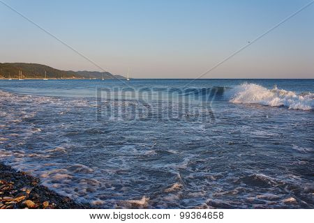 Waves on the beach against the backdrop of mountainous coast