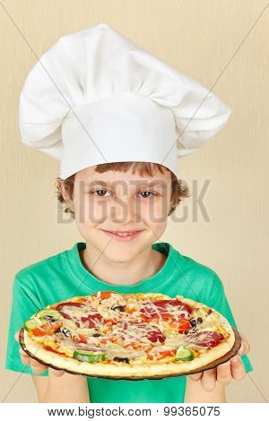 Young smiling boy in chefs hat with cooked homemade pizza