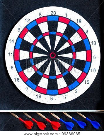 Dart board with 3 red darts and 3 blue darts