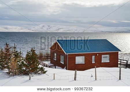 Simple house by the ocean with beautiful scenic landscape view across the bay in iceland