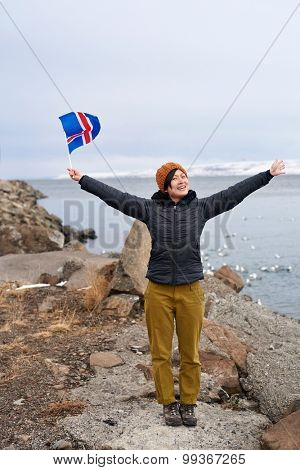 Young asian woman traveller posing with arms wide open in beautiful iceland landscape, waving flag carefree holiday vacation
