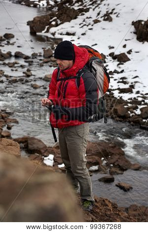 Active hiking man trekking by the river, using his mobile cell phone as a gps cold winter landscape snowy icy wilderness