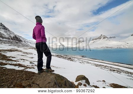 Active hiking woman looking at the view from the top of the snowy icy mountain fjord, enjoying the natural beauty landscape