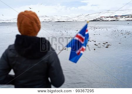 Carefree tourist enjoying the scenary scenic view across the water towards the mountains while waving iceland flag