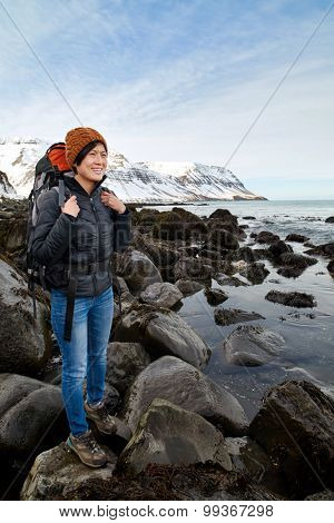 Asian woman traveller hiking with backpack along the ocean with large rocks, focus stacking technique