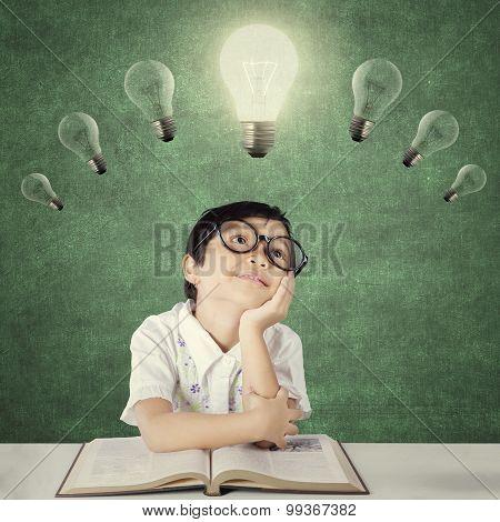 Child Thinks Inspiration Under Bright Light Bulb