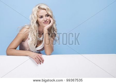 beauty, fashion and young woman in pink dress on blue background holding empty white board