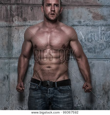 fitness male model with sixpack on the rustic wall