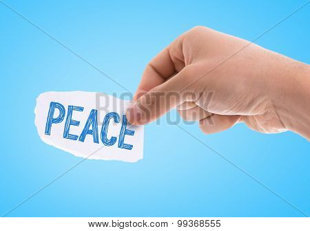 Piece of paper with the word Peace with blue background