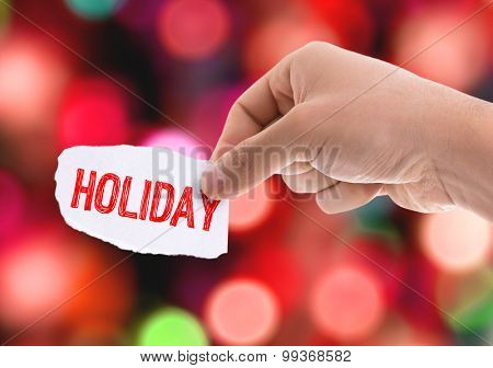 Piece of paper with the word Holiday with bokeh background