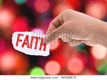 Piece of paper with the word Faith with bokeh background