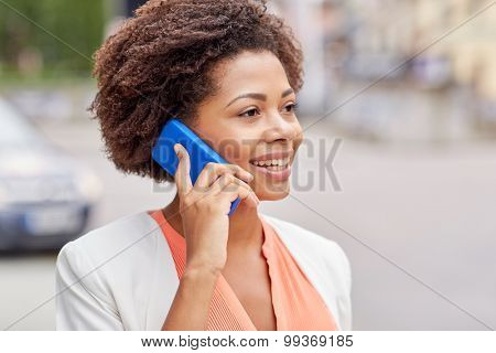 business and people concept - young smiling african american businesswoman in city