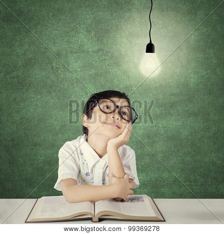Smart Primary School Student Looking At Light Bulb