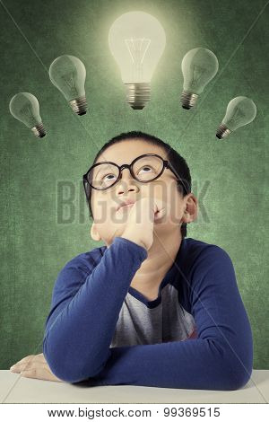 Thoughtful Male Student Under Light Bulb