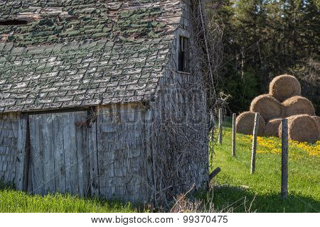 Haybales and an old barn sinking into the ground.