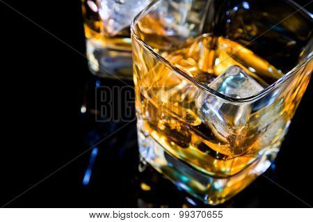 Close-up Of Top Of View Of Glass Of Whiskey On Black Table With Reflection