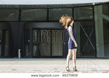 Young attractive woman turning his head waving hair, standing in the background of the business center.
