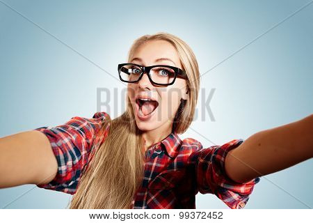 Close Up Portrait Of A Young Joyful Blonde Girl Holding A Smartphone Digital Camera With Her Hands A