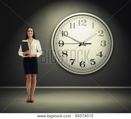 smiley businesswoman with black folder standing over grey wall with big white clock