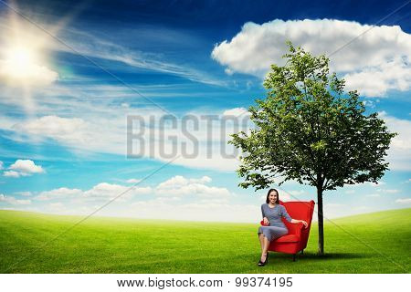 smiley young woman resting in red chair on green meadow near tree against blue sky