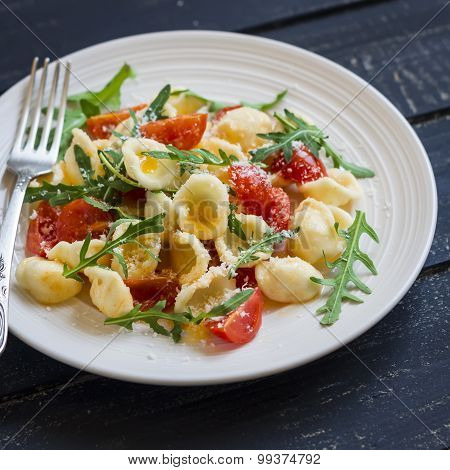 Orecchiette Pasta With Tomatoes, Parmesan And Rocket Salad On A Plate Light On A Dark Wooden Backgro