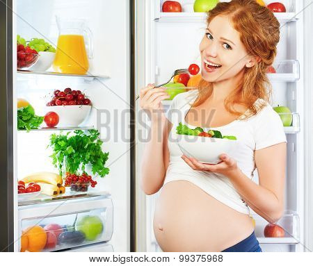 Happy Pregnant Woman Eating Salad Near Refrigerator